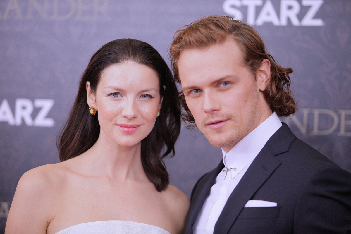 Outlander Caitriona Balfe and Sam Heughan pose for a photo at an awards show.