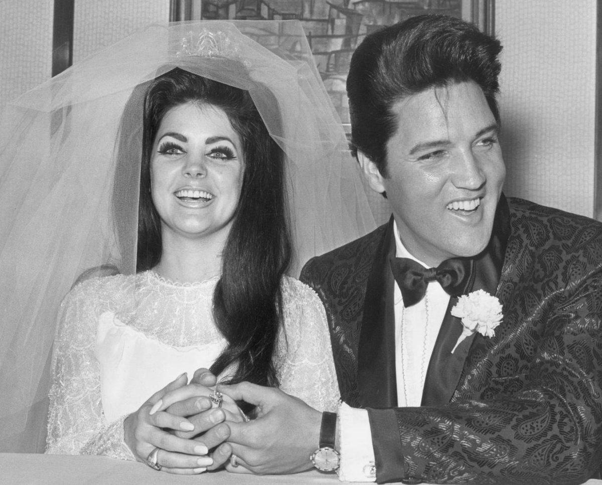 Rock and roll singer and actor Elvis Presley (1935 - 1977) holding hands with his bride, Priscilla Beaulieu Presley, on their wedding day, Las Vegas, Nevada.