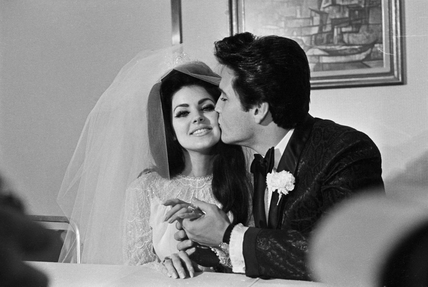 Las Vegas, NV: Elvis Presley gives his new bride, Priscilla Ann Beaulieu, a kiss following their wedding. The bride wears a large diamond on her finger.