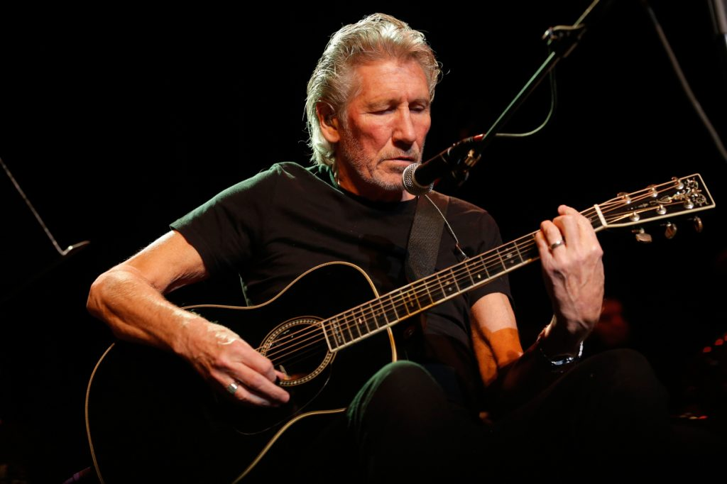Roger Waters playing guitar on stage