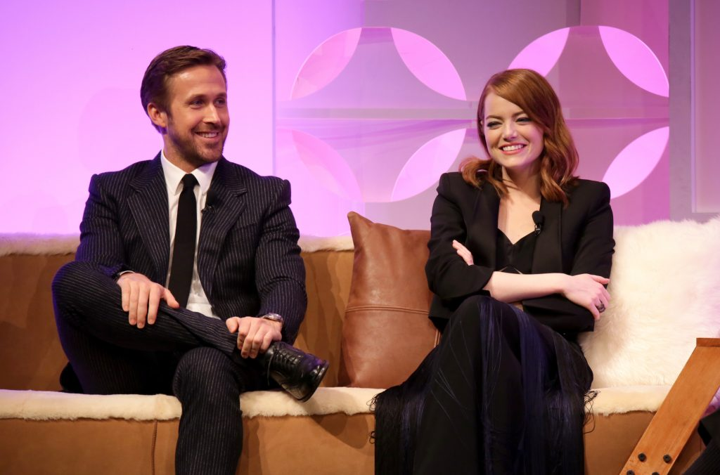(L-R) Ryan Gosling and Emma Stone smiling, sitting on a couch