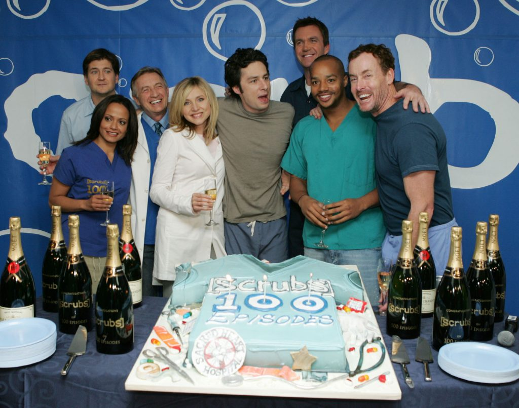 (L-R) Judy Reyes, producer Bill Lawrence, Ken Jenkins, Sarah Chalke, Zach Braff, Neil Flynn, Donald Faison and John C. McGinley smiling in front of a cake celebrating the 100th episode