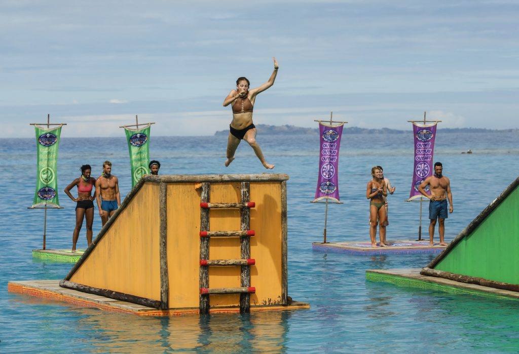 Survivor contestants competing on the show, in the water, with one contestant jumping off a platform