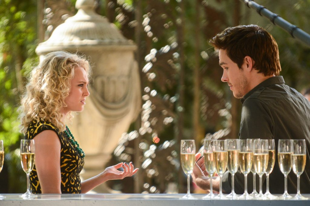 (L-R) AnnaSophia Robb and Chris Wood on 'The Carrie Diaries' standing in front of a bar