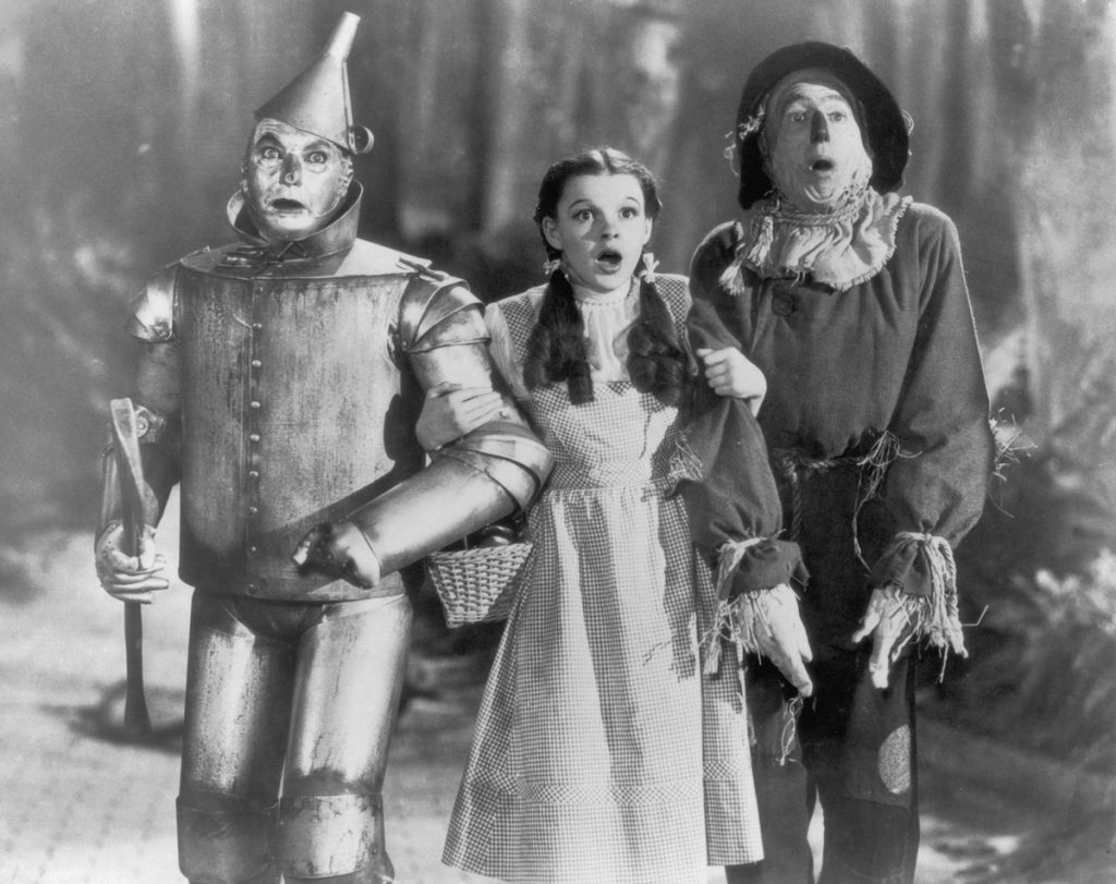 The Tin Man (Jack Haley), Dorothy (Judy Garland) and the Scarecrow (Ray Bolger) set off on their quest for fulfillment in the children's classic 'The Wizard of Oz', directed by Victor Fleming for MGM, 1939