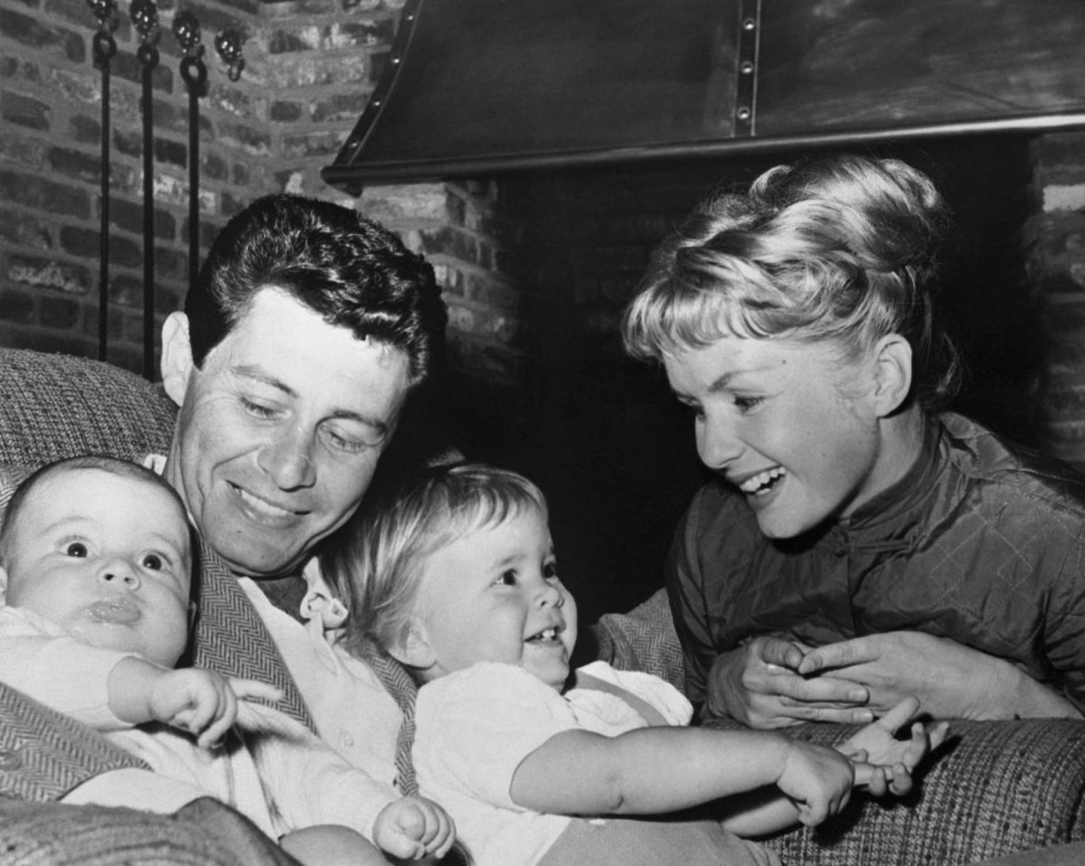 """(Original Caption) Hollywood: A newcomer to the ranks of fatherhood, Eddie Fisher was named """"Father of the Year in TV"""" by the National Father's Day Committee. Mrs. Fisher (Debbie Reynolds) and the children presented Fisher with a handsome photo wallet containing their pictures. Carrie Frances is 19 months and son Todd (L) is 4 months old."""