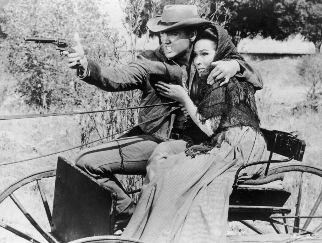 Elvis Presley holding a woman and a gun