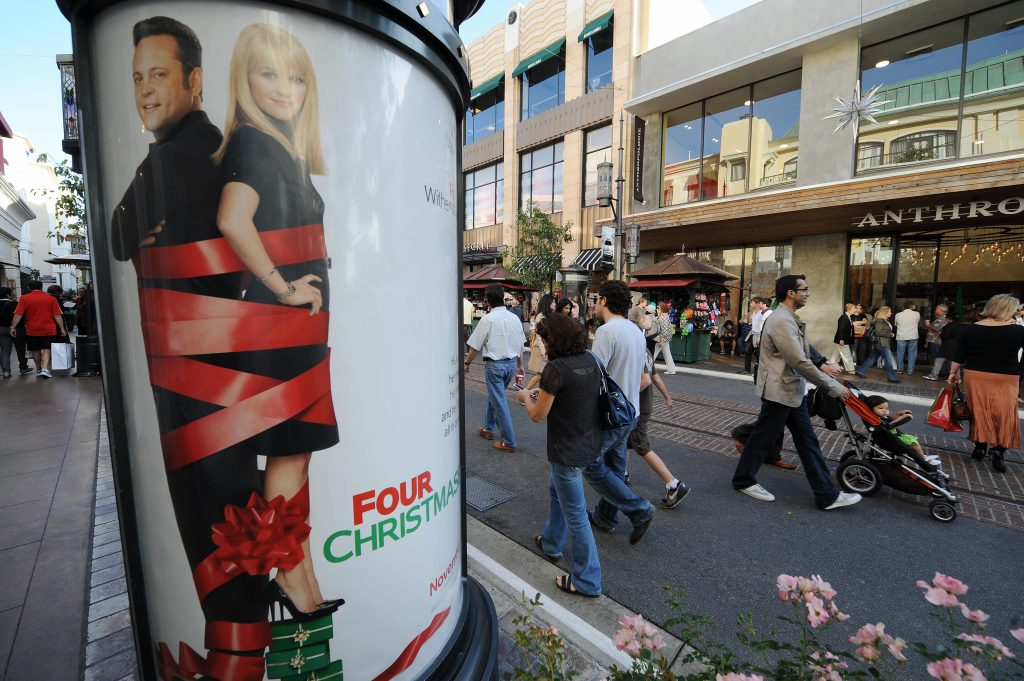 """People walk past a poster advertising """"F"""