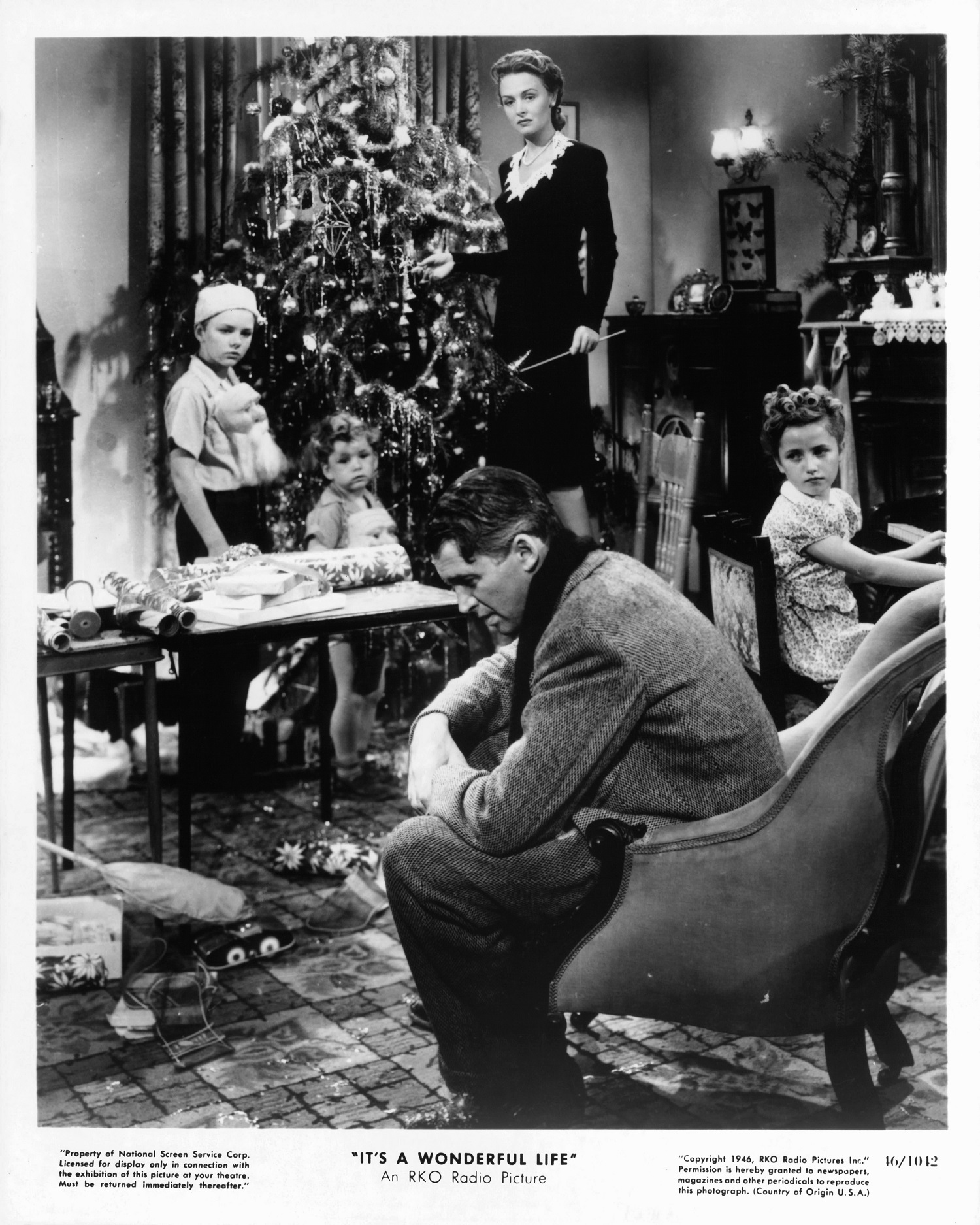 James Stewart sits while Donna Reed looks to him in a scene from the film 'It's A Wonderful Life'