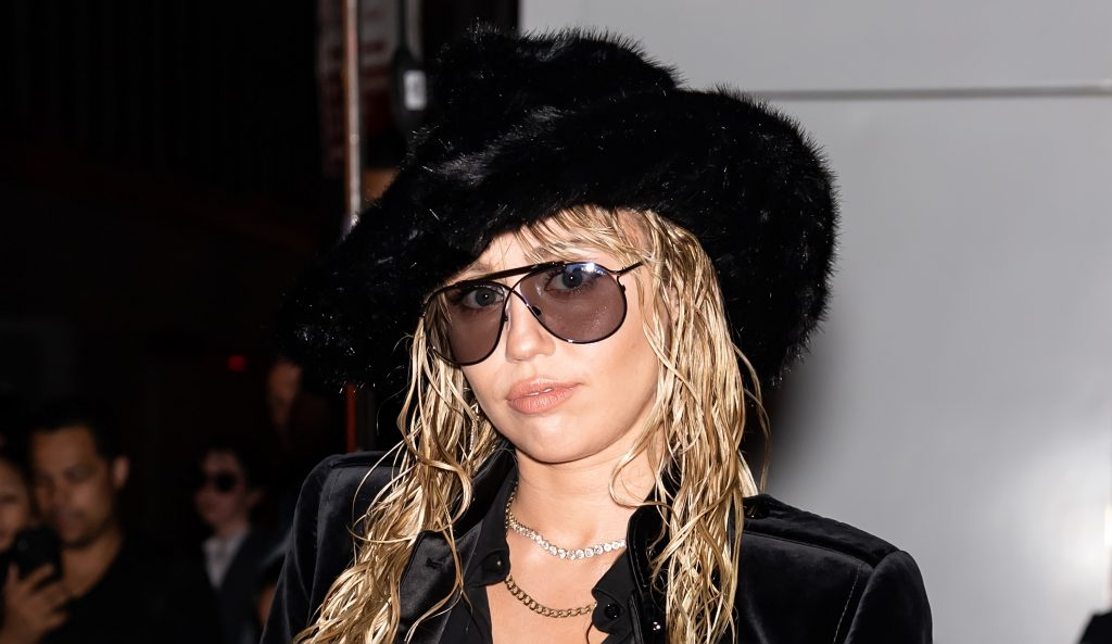 Miley Cyrus wearing a large black hat