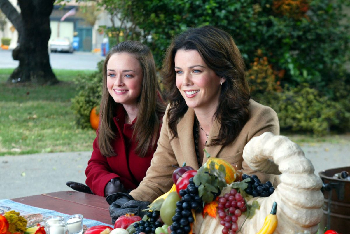 Alexis Bledel and Lauren Graham sit in Stars Hollow's town square in a scene for 'Gilmore Girls'