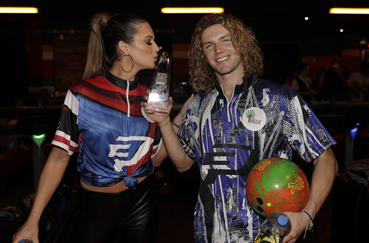 """""""Big Brother"""" stars Angela Rummans kisses the trophy that Tyler Crispin won during the 2019 State Farm Chris Paul PBA Celebrity Invitational"""