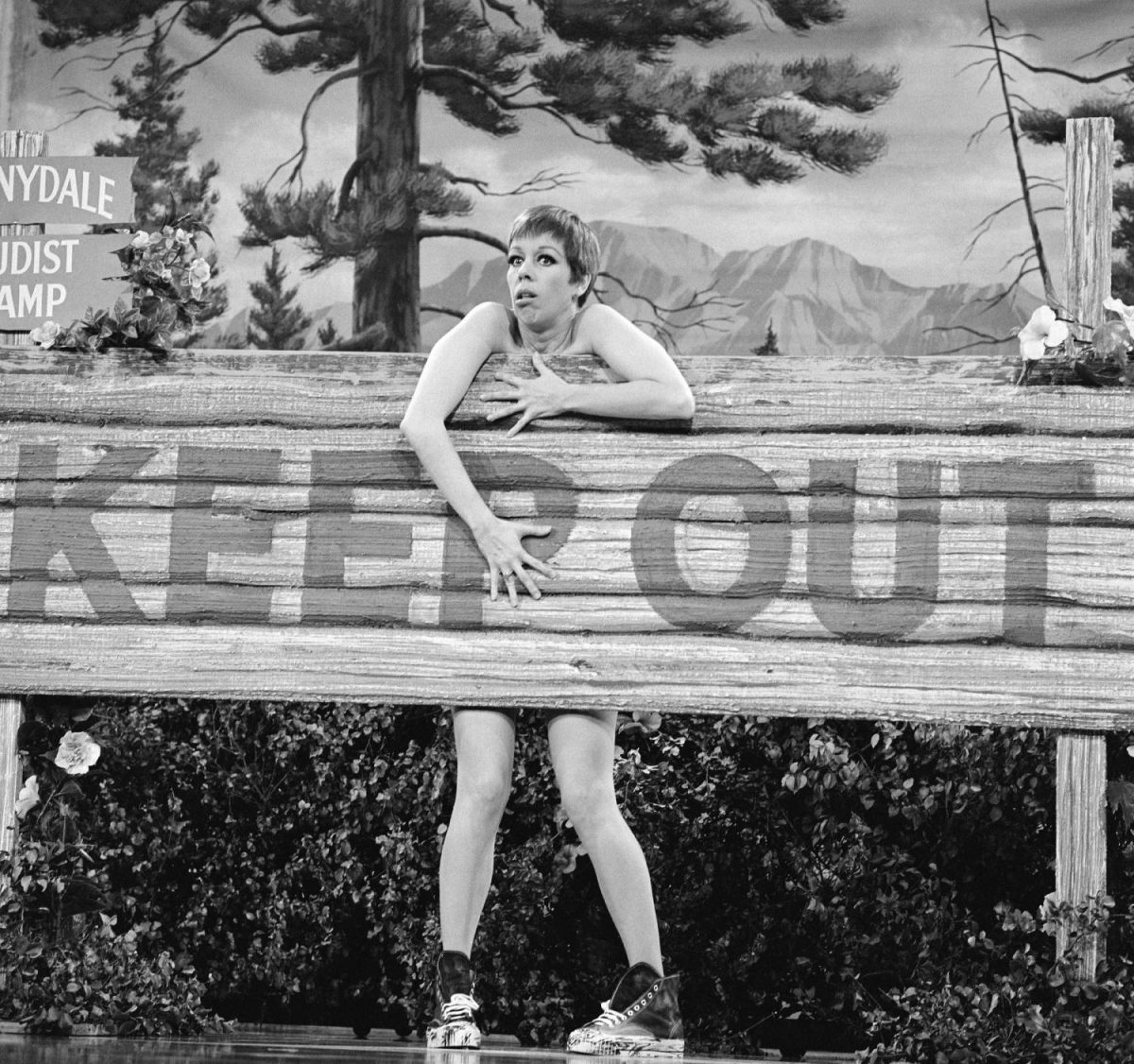 Seemingly naked, American comedienne and actress Carol Burnett hides behind a large wooden sign labelled 'Keep Out' during a skit on 'The Carol Burnett Show,' October 28, 1967.