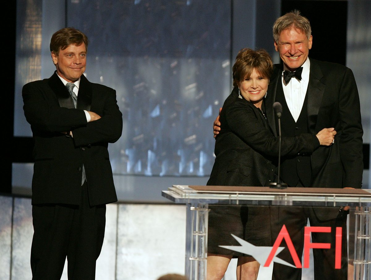 HOLLYWOOD - JUNE 09: (L-R) Actors Mark Hamill, Carrie Fisher and Harrison Ford speak onstage during the 33rd AFI Life Achievement Award tribute to George Lucas at the Kodak Theatre on June 9, 2005 in Hollywood, California.