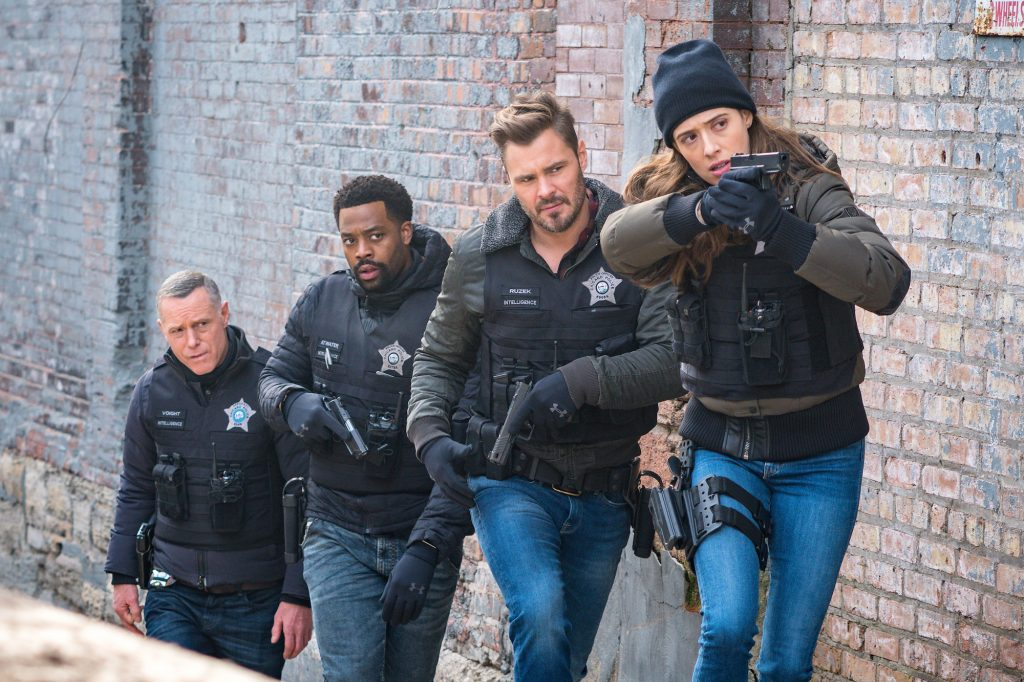 (L-R) Jason Beghe as Hank Voight, LaRoyce Hawkins as Kevin Atwater, Patrick John Flueger as Adam Ruzek, Marina Squerciati as Kim Burgess lined up in front of a brick building with guns drawn on 'Chicago P.D.'