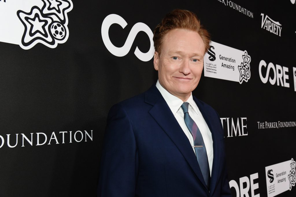 Conan O'Brien smiling in front of a black background