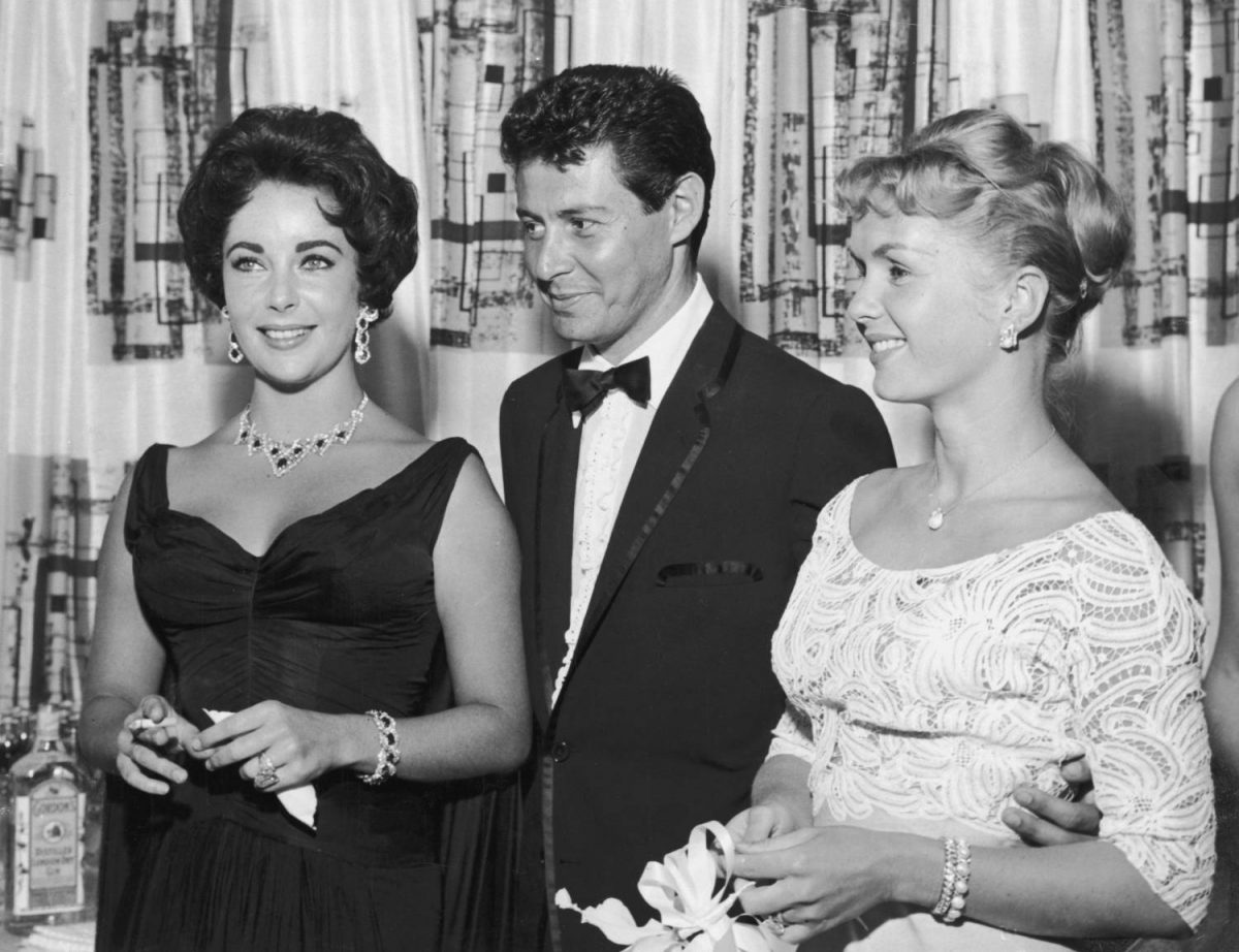 1958: American singer Eddie Fisher, wearing a tuxedo, stands with arm around his wife, American actor Debbie Reynolds (R) and smiles while looking at British-born actor Elizabeth Taylor, smoking a cigarette, Las Vegas, Nevada. The next year Fisher left Reynolds and married Taylor