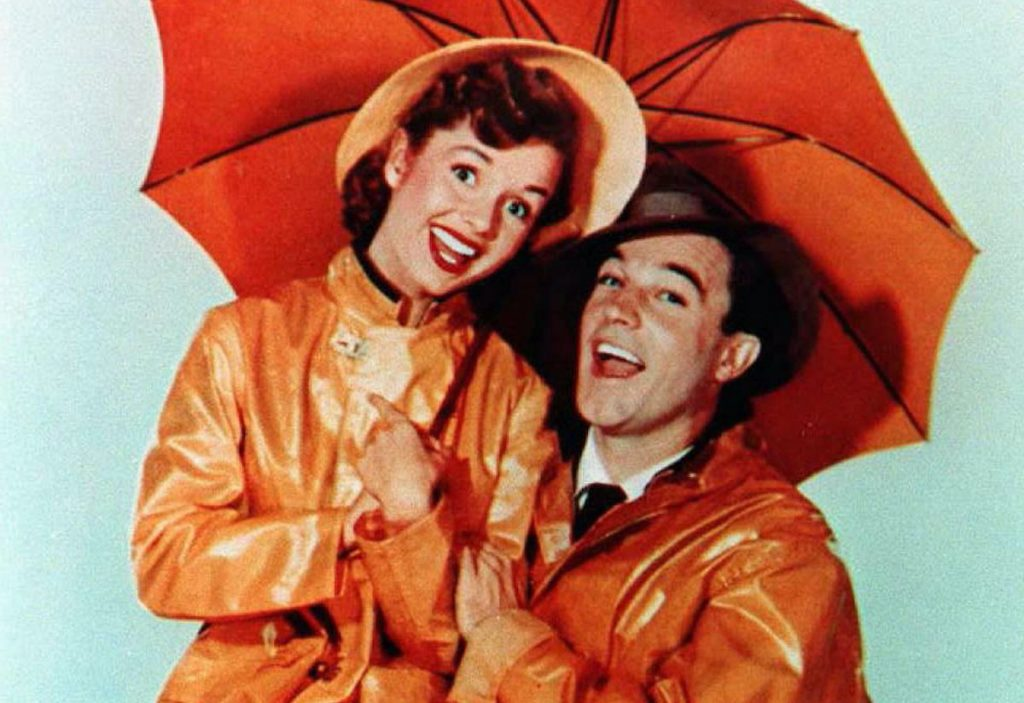 Debbie Reynolds (L) and Gene Kelly (R) in a promotional image for 'Singin' in the Rain' (1952) | FILE/AFP via Getty Images