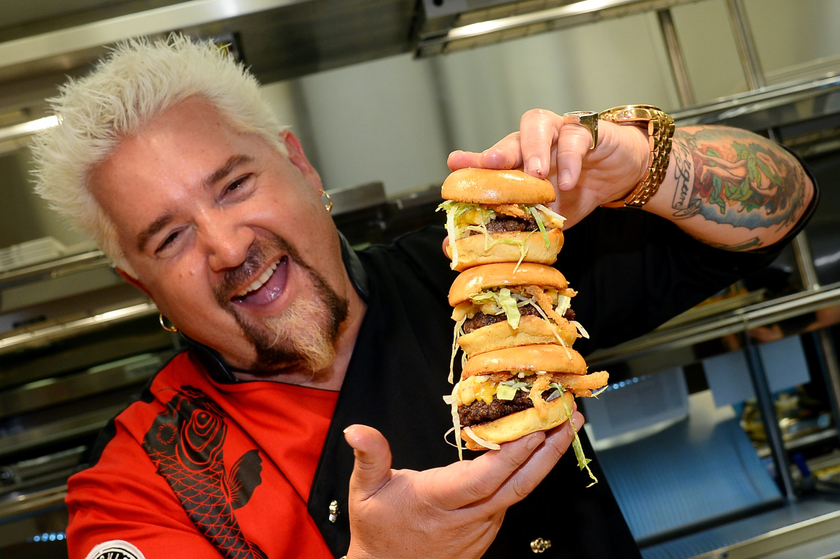 Chef and television personality Guy Fieri holds hamburgers in the kitchen during a welcome event for Guy Fieri's Vegas Kitchen & Bar at The Quad Resort & Casino on April 4, 2014 in Las Vegas, Nevada. The restaurant opens on April 17