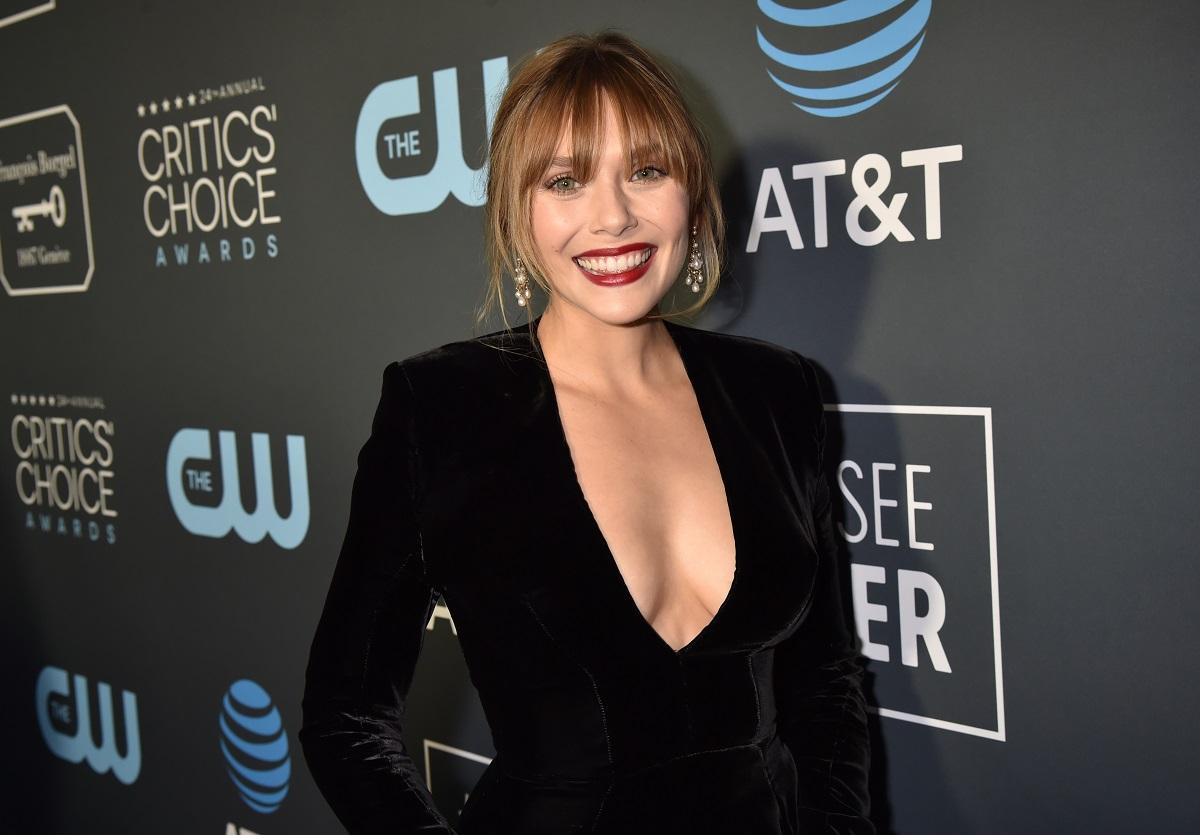 Elizabeth Olsen in front of a Critics' Choice Awards backdrop dressed in black
