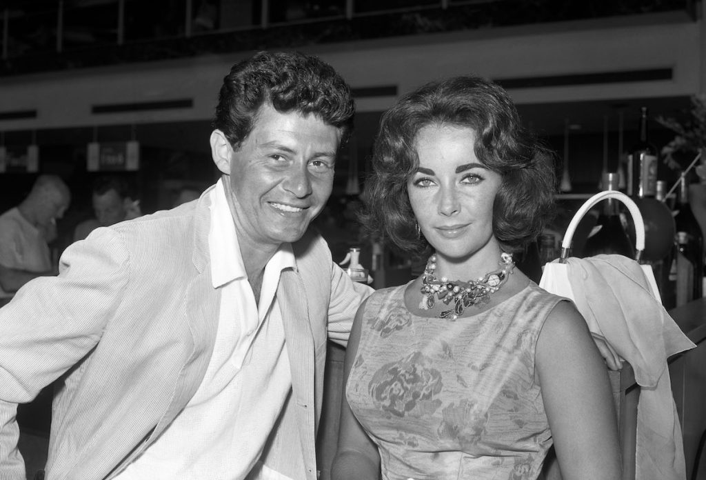 Singer Eddie Fisher and his wife, film star Elizabeth Taylor, on arrival at London Airport, from a holiday in Nice | PA Images via Getty Images