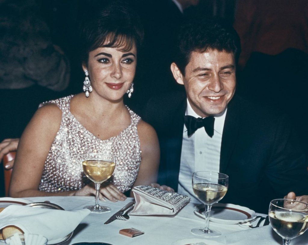 Elizabeth Taylor and Eddie Fisher dining at an event, circa 1959. Taylor wears a silver beaded dress.