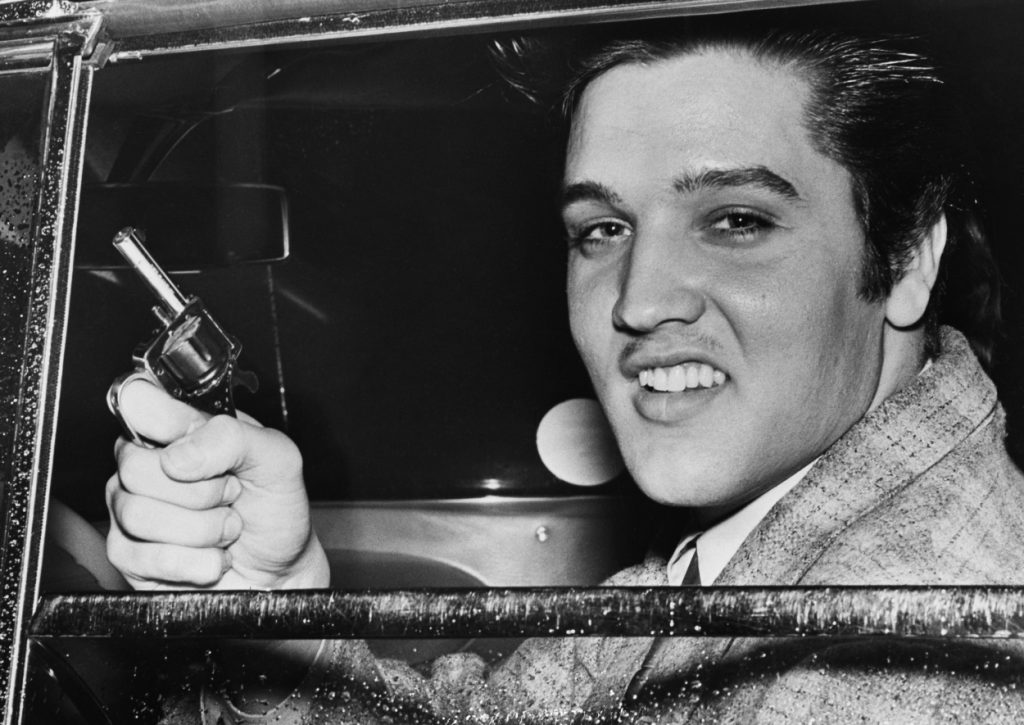 Elvis Presley smiles from a car holding a toy gun