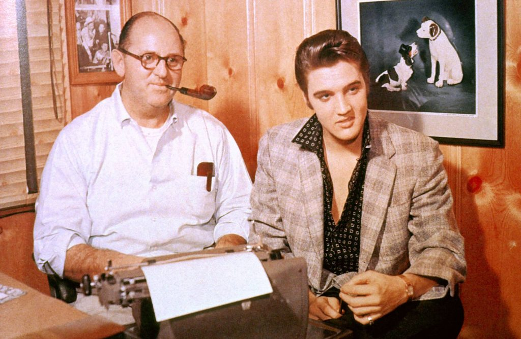 (L-R) Colonel Tom Parker, smoking a pipe, and Elvis Presley smiling