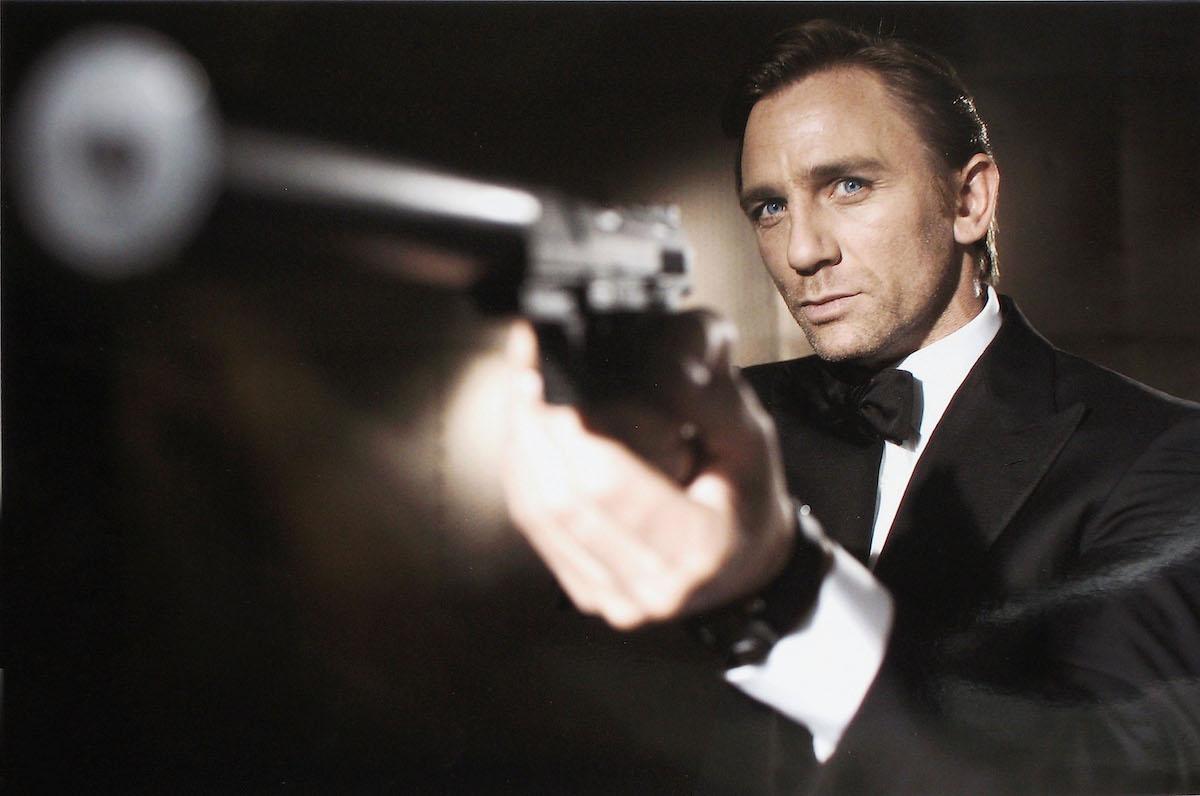 Daniel Craig poses as James Bond holding a gun