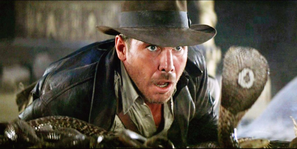 Harrison Ford as Indiana Jones facing a cobra snake in the Well of the Souls chamber. Initial theatrical release June 12, 1981.