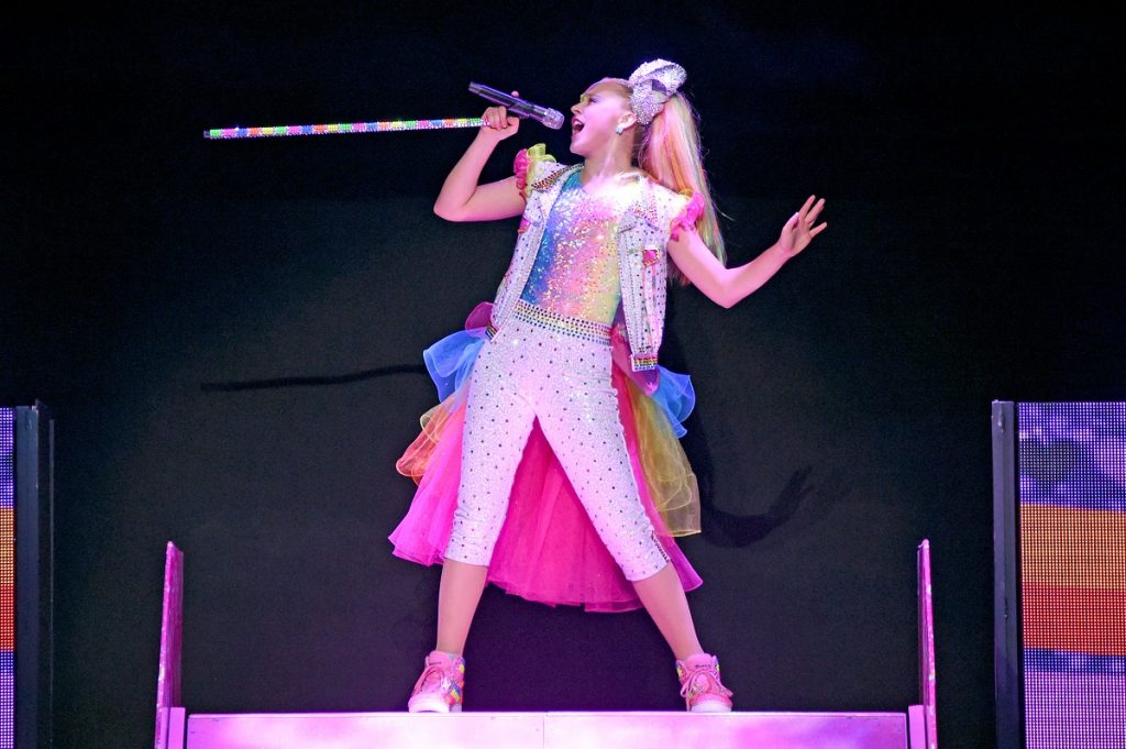 JoJo Siwa sings on stage in a colorful outfit