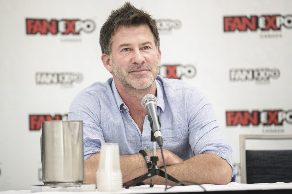 Joe Flanigan smiling in front of a white background with repeating logos