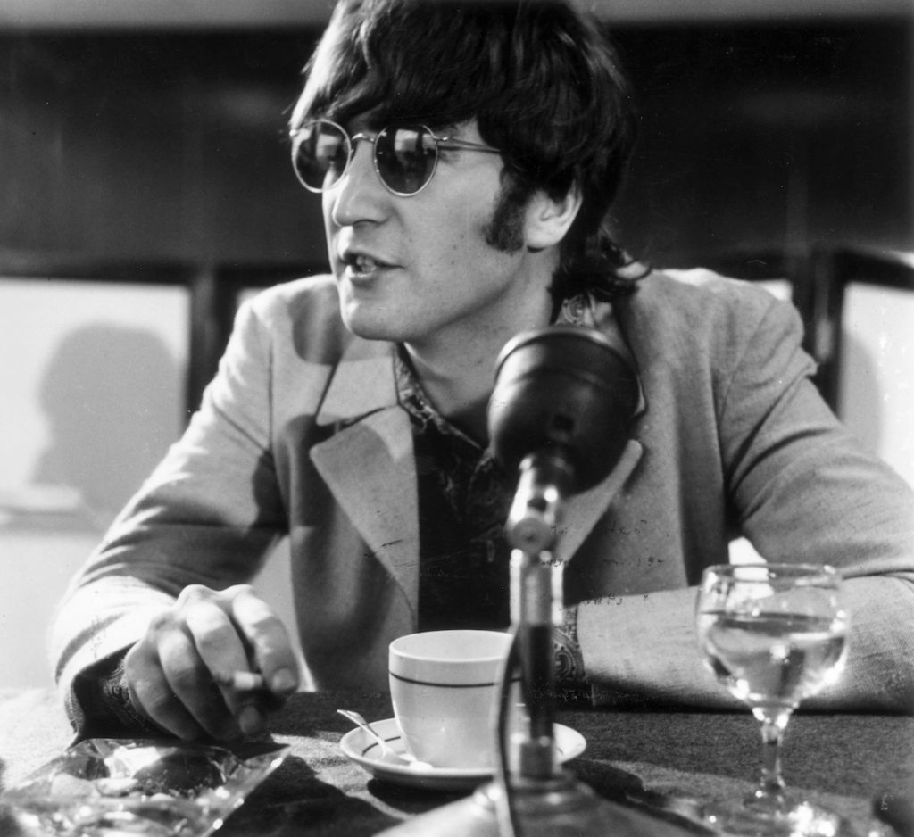 John Lennon (1940 - 1980) at a press conference at London Airport after the Beatles' return from Manila.