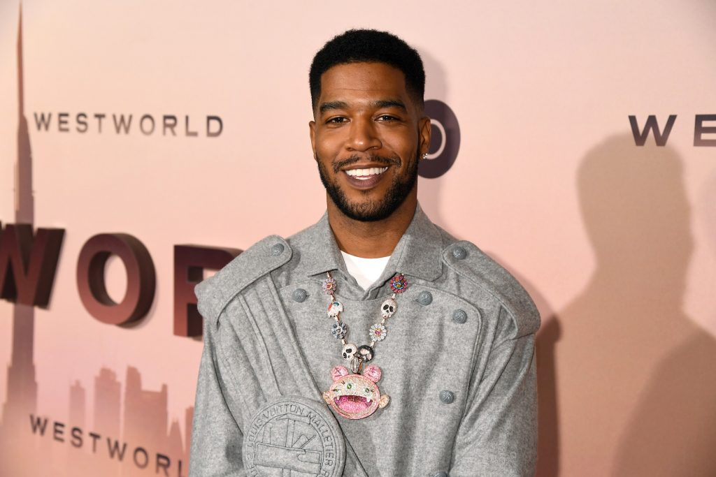 Scott 'Kid Cudi' Mescudi smiling in front of a pink background