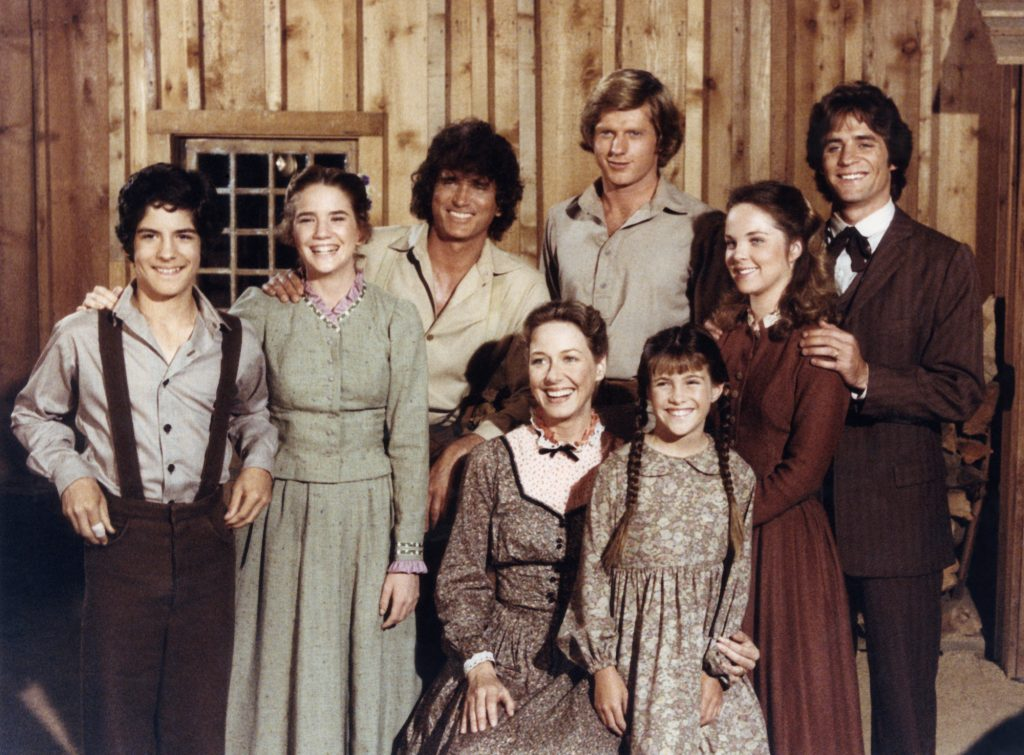 (Top L-R) Matthew Laborteaux as Albert Quinn Ingalls, Melissa Gilbert as Laura Elizabeth Ingalls Wilder, Michael Landon as Charles Philip Ingalls, Dean Butler as Almanzo James Wilder, Melissa Sue Anderson as Mary Ingalls Kendall, Linwood Boomer as Adam Kendall (Bottom L-R) Karen Grassle as Caroline Quiner Holbrook Ingalls, Lindsay/Sidney Greenbush as Carrie Ingalls smiling in front of a wood paneled background