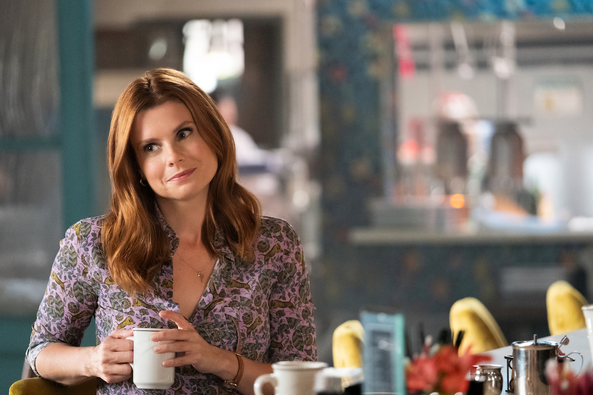 JoAnna Garcia Swisher tilting head and holding coffee cup in Sweet Magnolias