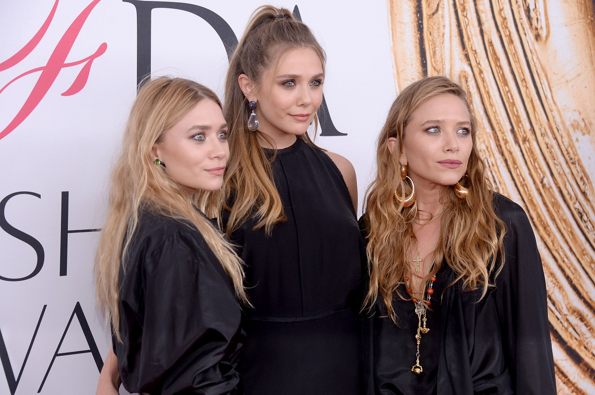 Elizabeth Olsen standing in the center of Mary-Kate and Ashley Olsen with all of them dressed in black