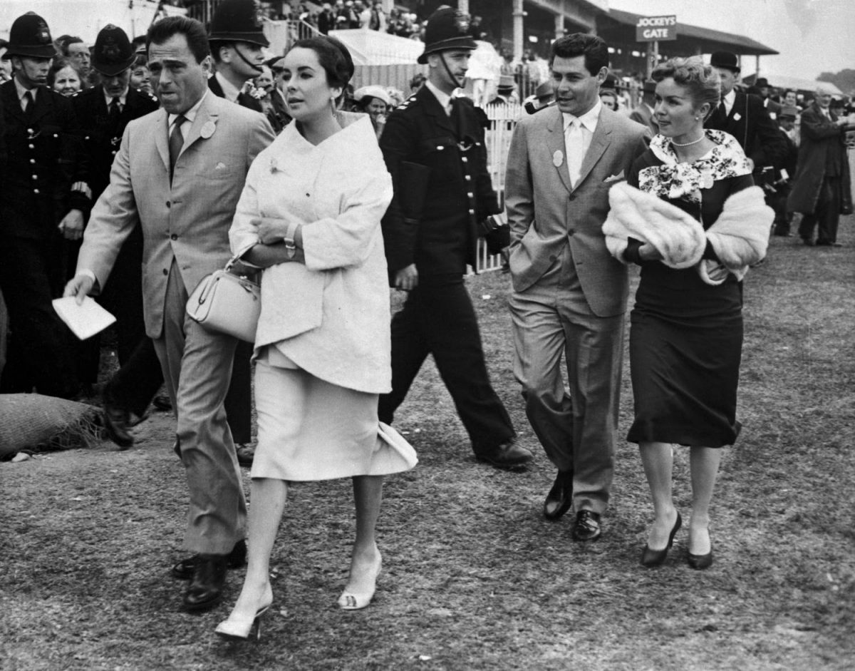 Actress elizabeth Taylor, who nearly died of pneumonia less than a year ago, was hospitalized late 2/17 with a throat hemorrhage, according to unconfirmed reports. In this June 5, 1957 photo, miss Taylor is shown with late husband, Mike Todd(left) as they attended the running of the English Derby in Epsom. They are followed by singer, Eddie Fisher, and his wife, Debbie Reynolds.