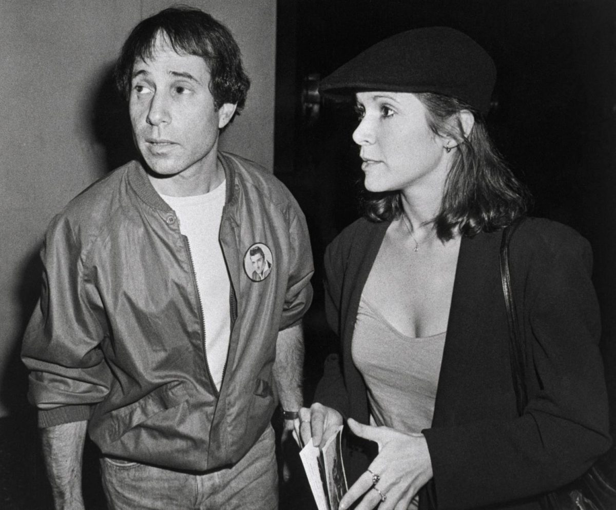 "(Original Caption) 6/3/1980-New York: Singer-composer Paul Simon and actress Carrie Fisher at a reception following a private screening of the movie ""Carney,"" which stars Gary Busey"