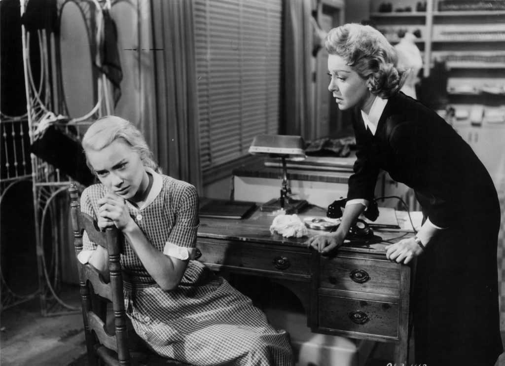 (L-R) Hope Lange sitting on a chair and Lana Turner checking on her in 'Peyton Place' (black and white)