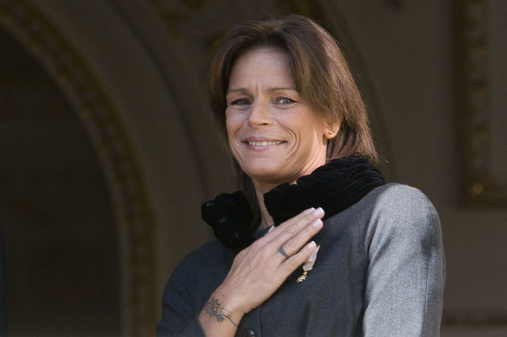 Princess Stephanie of Monaco, smiling, touching her shoulder
