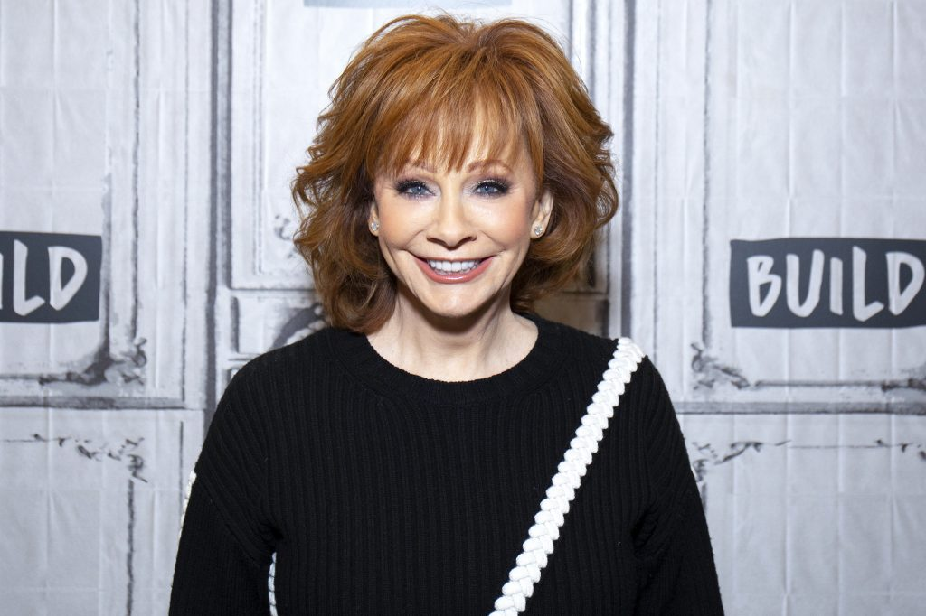 Reba McEntire smiling in front of a white background