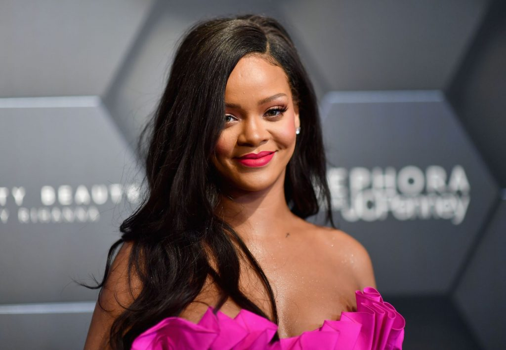 Rihanna smiling in front of a blurred black background