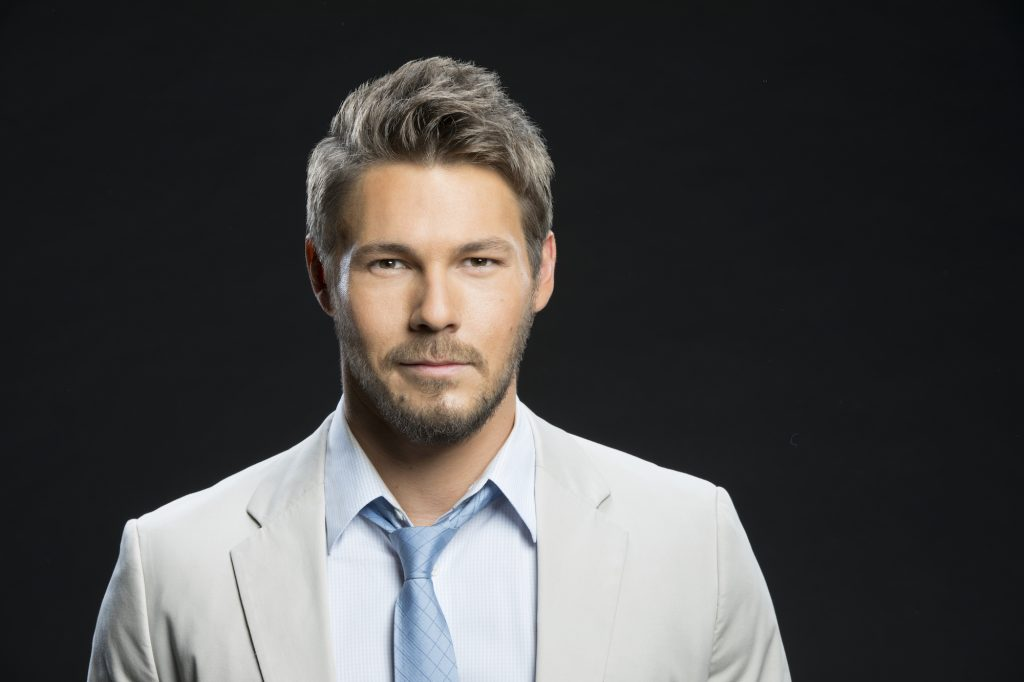 Scott Clifton smiling in front of a black background