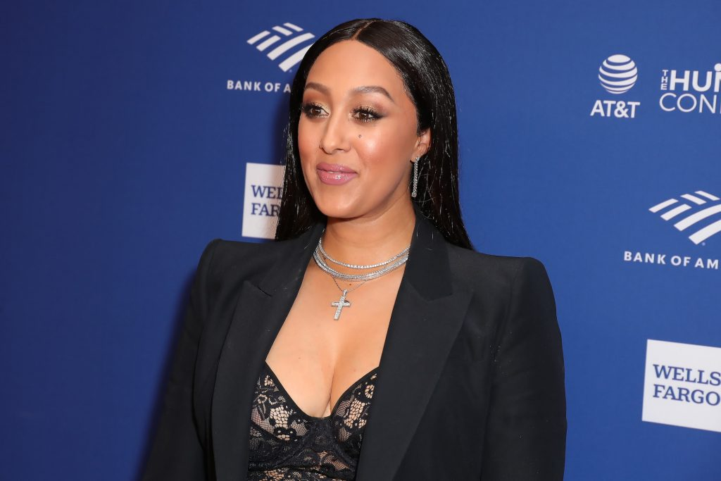 Tamera Mowry-Housley smiling in front of a blue background