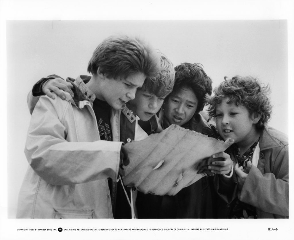 L to R: Corey Feldman, Sean Astin, Ke Huy Quan and Jeff Cohen reading a treasure map in a scene from the film 'Goonies', 1985.
