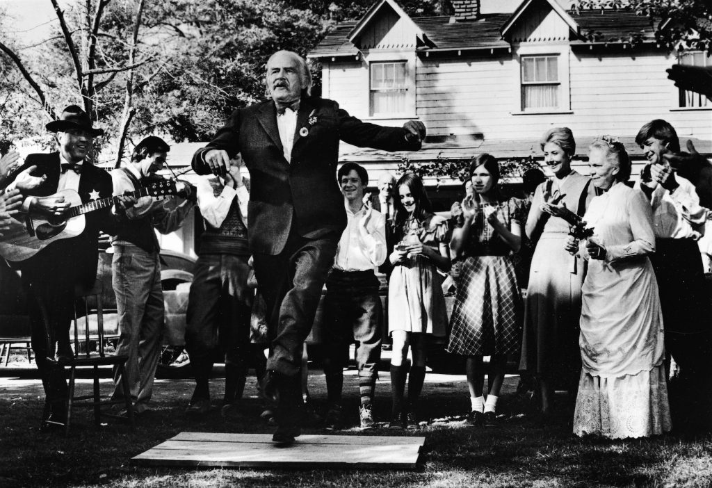 Actor Will Geer as Grandpa Walton dancing a jig in front of the Walton house on 'The Waltons'