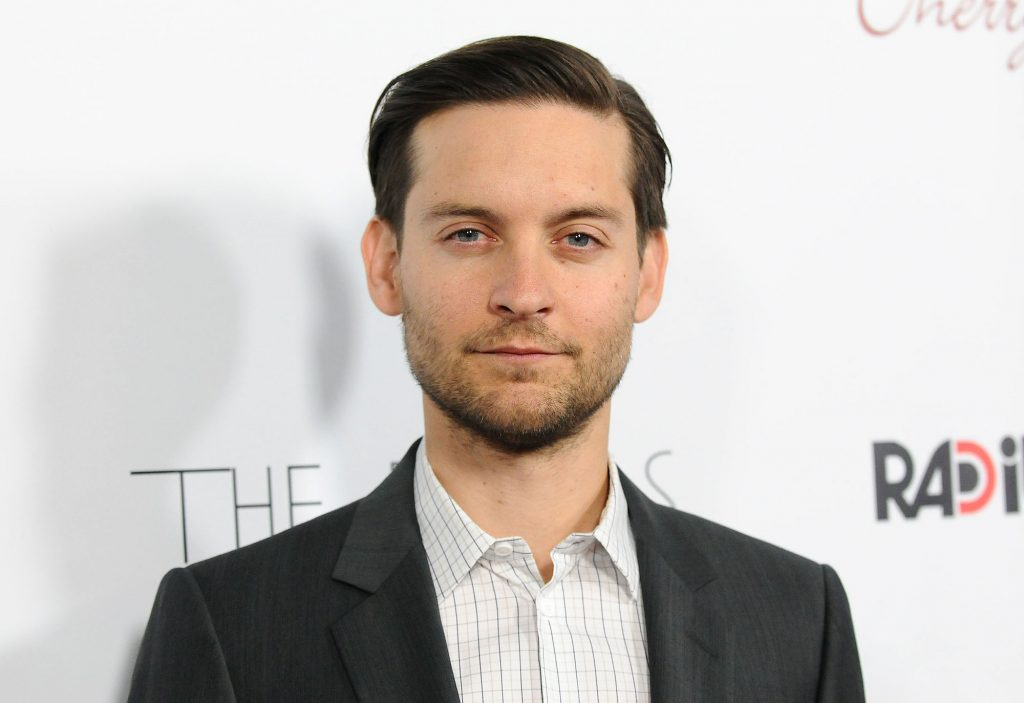 Tobey Maguire smiling in front of a white background