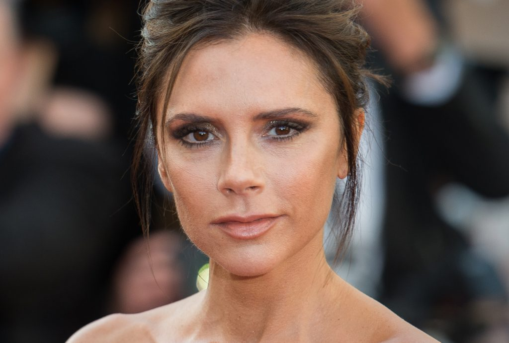 Victoria Beckham smiling in front of a blurred crowd
