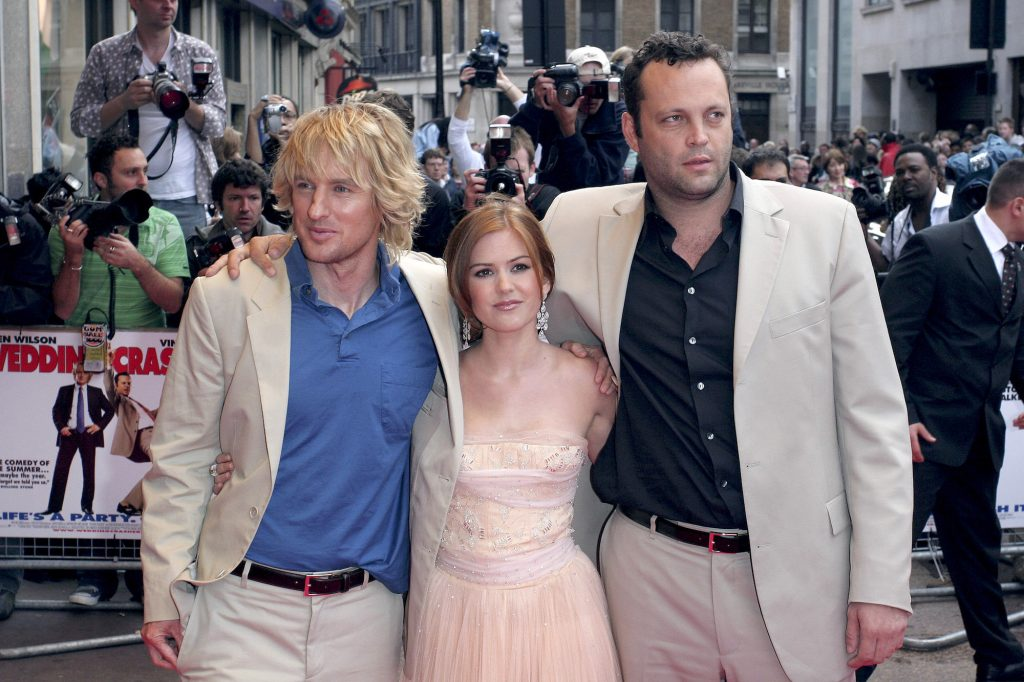 (L-R) Owen Wilson, Isla Fisher, and Vince Vaughn smiling in front of a crowd